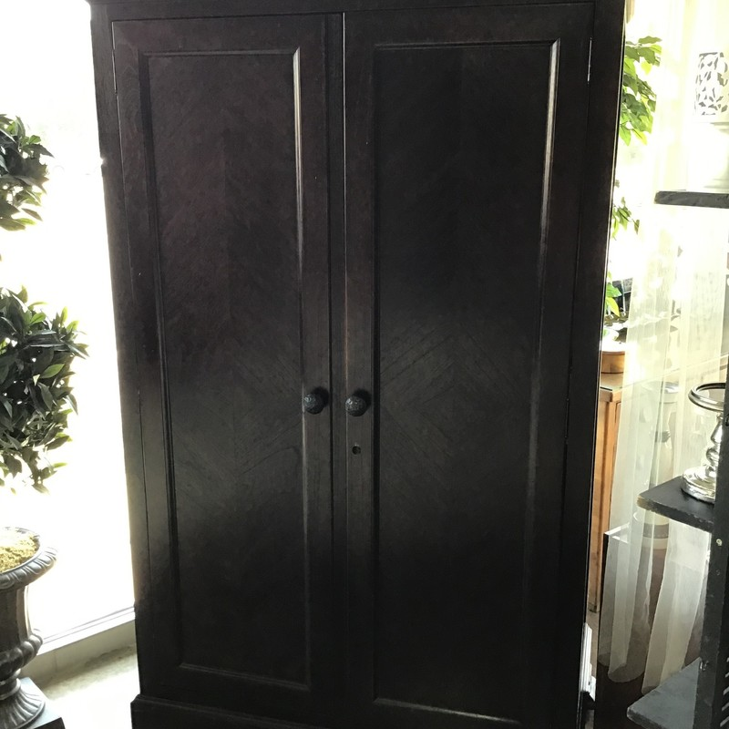 "This beautiful dark wood armoire by Arhaus has 2 doors that open to reveal tons of storage! There is space at the top to add a clothing bar and you can remove the top shelf. There are 2 drawers and then additional shelving below. The hardware is hammered iron and the piece comes with a working key. It could also be used as a television armoire, as there are holes in the back for cords. This item is 1 piece, so it doesn't separate for moving.<br /> Dimensions are 47"" x 28"" x 77""."
