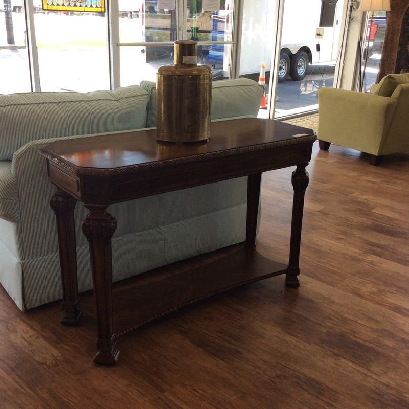 This sofa table by Ashley features a dark wood finish,  lovely woodcarving details and a bottom tier for additional display space. Good condition.