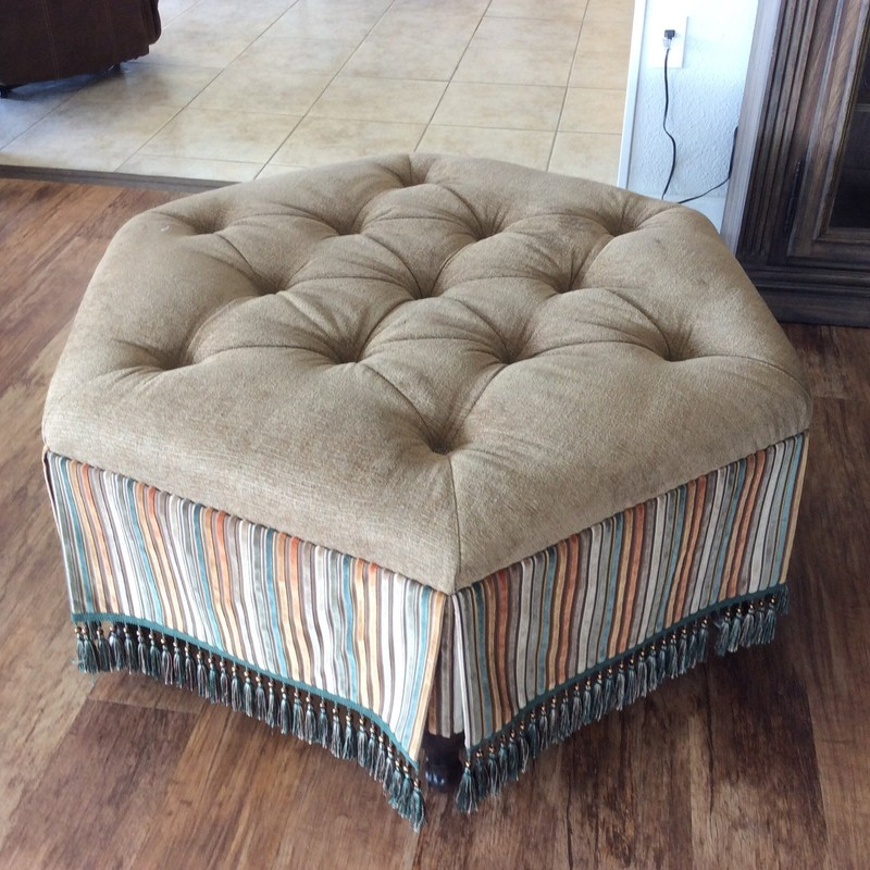 This MARKOR INTERNATIONAL ottoman actually came in with a matching sofa and chair, that are available for purchase seperately. This piece features a hexagonal shape with a tufted tan chenile top cushion. There are also tassles all around the bottom of the skirt.