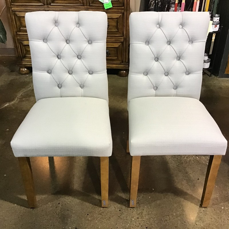 This pair of beautiful Tufted Dining Chairs knows how to make an entrance with its richly detailed design, complete with elegant diamond tufting. Set on a chic wooden frame, this light grey chair is a charming addition to any space whether you're pulling it up to your kitchen table or using it as a seat in front of your vanity.<br /> <br /> Matches:  #8905, #8906, #8908