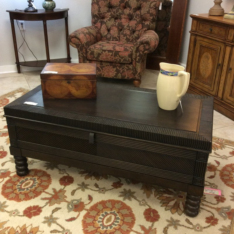 This is a combination of beauty and function! It is both a coffee table and a trunk. By Bassett, it features a dark wood finish, espresso in color and provides a ton of storage space on the inside.