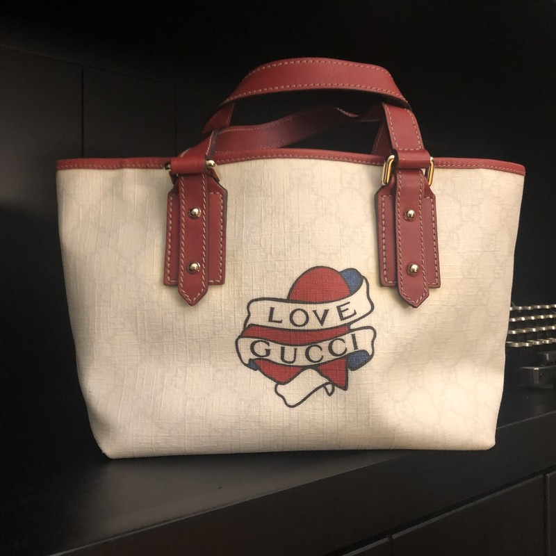 "Gucci GG Canvas Tatoo Tot, White, Size: Small<br /> Red lined Gucci Tatto Tote. This wildly popular bag measures 7"" tall, 12"" wide and 5"" deep. short tote straps drop 4.5 inches. some yellowing on bottom of bag, otherwise very good condition."