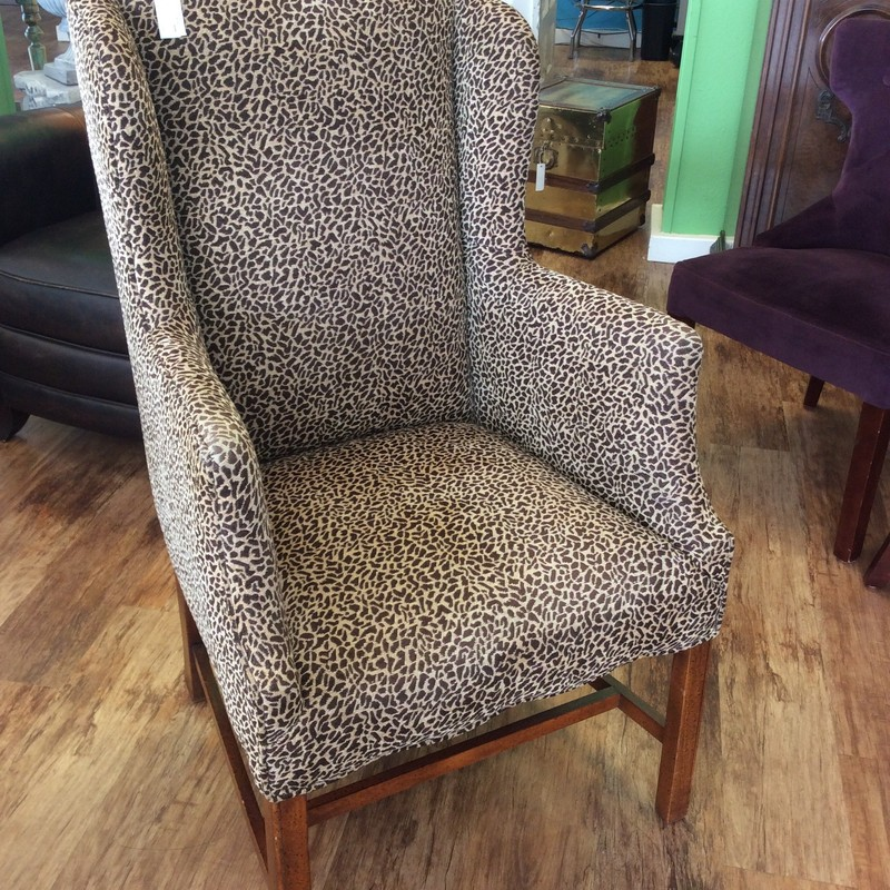 This wing back chair  has a leopard print upholstery in black and tan. Comfortable and in good condition.