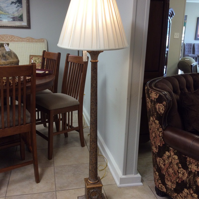 This is a lovely floor lamp. It features a pedestal base supporting a long, slender column. It has been faux painted copper and black and has a weathered, vintagy look. Topped by an off-white pleated shade.