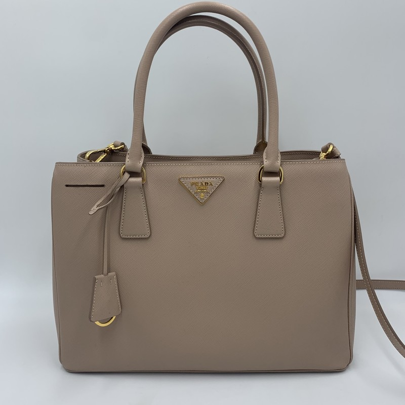 "Prada Saffiano Lux Satche, Mauve, Size: L<br /> <br /> condition: EXCELLENT. Miniscule scuff on bottom<br /> Original dust bag included<br /> <br /> original retail: $1900<br /> <br /> 12.5""W x 9""H x 5""D at base<br /> 6"" handle drop<br /> 23"" +/- strap drop (adjustable)<br /> <br /> We guarantee the authenticity of every bag on our site. Each bag comes with either an original sales receipt or a Certificate of Authenticity from AuthenticateFirst.com. Established in 2013, AuthenticateFirst.com<br /> (http://authenticatefirst.com) is one of the premier authentication services in the US, providing authentications of designer handbags, wallets, small leather goods, footwear, jewelry, and accessories. They employee in-house experts who have decades of experience working with hundreds of luxury brands."
