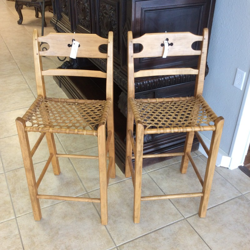 This is a very unusual looking pair of handcrafted chairs. They feature solid wood construction that looks like either pine or maple. The seats are made of rawhide strips in caned pattern. Very petite in stature and suprisingly comfortable!