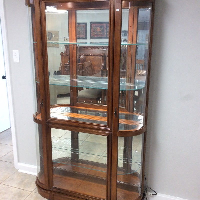 This is a pretty, older style, lighted, curio cabinet. It features solid medium oak construction and has 4 shelves (3 of which are adjustable). The curved glass doors are what sets this curio apart from it's peers. At only $495, it'll be gone in no time!