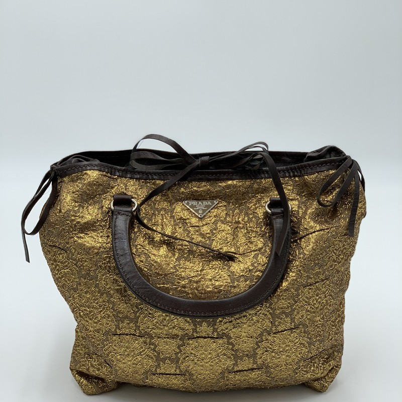 "Prada Brocade Handbag, Gold, Size: S<br /> <br /> condition: GOOD. splitting on leather ties<br /> <br /> 11""W x 9""H 1""D<br /> 3"" handle drop<br /> <br /> We guarantee the authenticity of every bag on our site. Each bag comes with either an original sales receipt or a Certificate of Authenticity from AuthenticateFirst.com. Established in 2013, AuthenticateFirst.com<br /> (http://authenticatefirst.com) is one of the premier authentication services in the US, providing authentications of designer handbags, wallets, small leather goods, footwear, jewelry, and accessories. They employee in-house experts who have decades of experience working with hundreds of luxury brands."