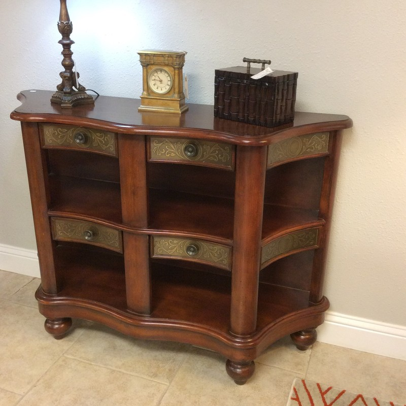 This entryway table is lovely! It features a dark wood finish and has 2 tiers for displaying. The 4 drawers and 2 sides have metal scrollwork fascia with vintagy brushed hardware. The top outside edge is slighlty scalloped.