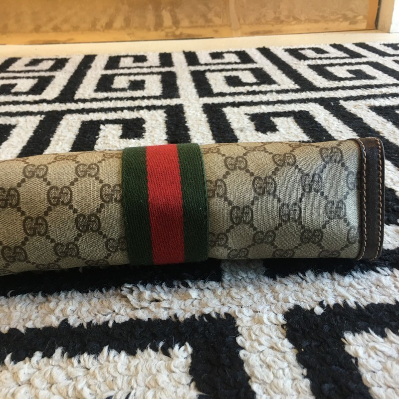 GORGEOUS, LIKE NEW Vintage Gucci clutch bag. Brown monogram with brown leather trim and classic red and green stripe. Vinyl interior. Has certificate of authenticity. Zero signs of use, no scuffs, tears, or staining. Looks brand new. Retail: $1,400. WON'T LAST!