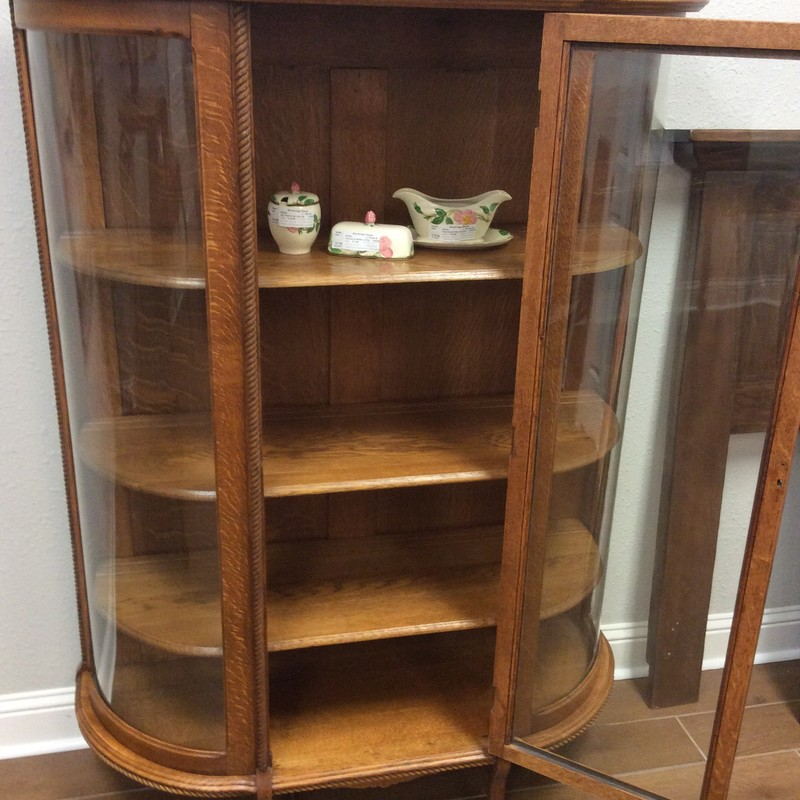 This little ANTIQUE curio is so adorable! It is constructed entirely of gorgeous tiger oak and there are 3 adjustable shelves inside. What makes this piece exceptional are the curved glass side panels, the miniature barley twist accents and the little tiny casters on each leg.