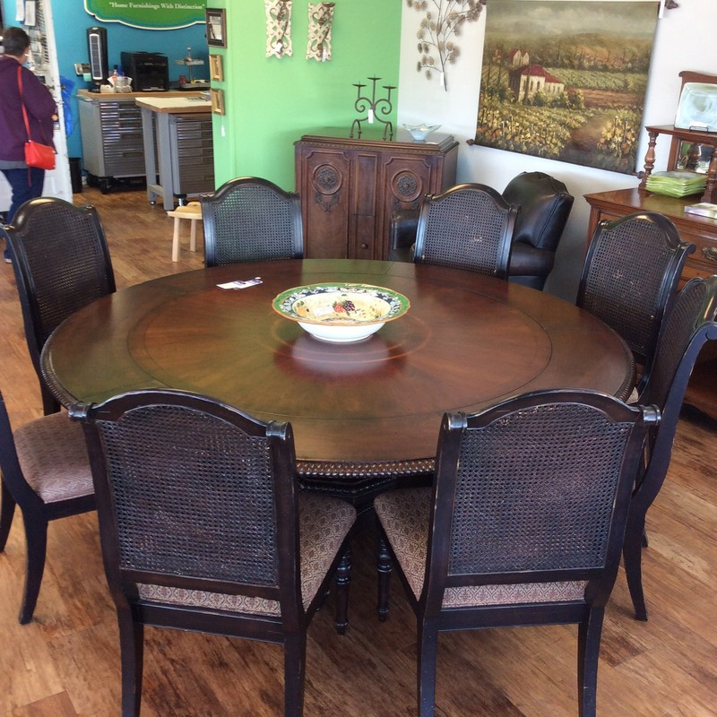 "This is a stunner!! This dining room set by Lexington would be the perfect set for your holiday gatherings. It measures 60"" in diameter but with the addition of 5 perimeter leaves it expands to 80"". It sports a rich, dark wood finish but perhaps it's most eye-catching feature is the pedestal base. Large with intricate woodwork, it has been distressed and antiqued giving it that vintagy, weathered look. Six chairs are included with a lovely upholstered seat . The seatback features a black double cane that is gorgeous. They too have a dark wood finish and have been distressed. Pictures aren't going to do this set justice, you need to come in and see it for yourself!"