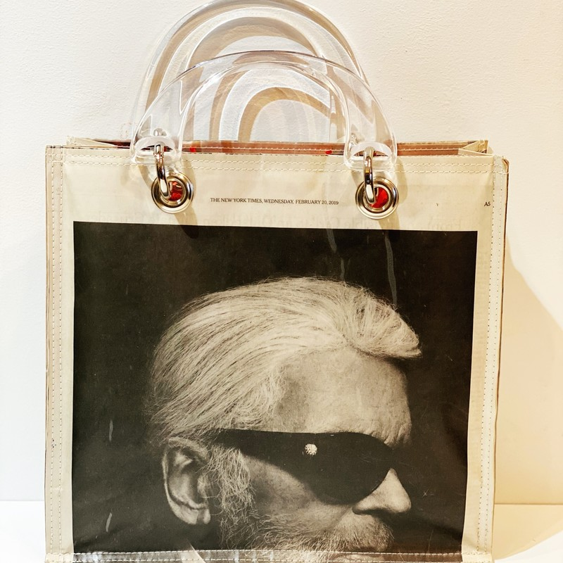 "Karl Lagerfeld Newspaper, NEW, Size: 11.5"" x 11"" x 4""<br /> With lucite handles. The Stella is our largest bag --  great for a day out touring or shopping.  Snap closure and inside pocket to carry your essentials.<br /> New bag made from Post Consumer Newspaper by hand in Lynn, Ma"
