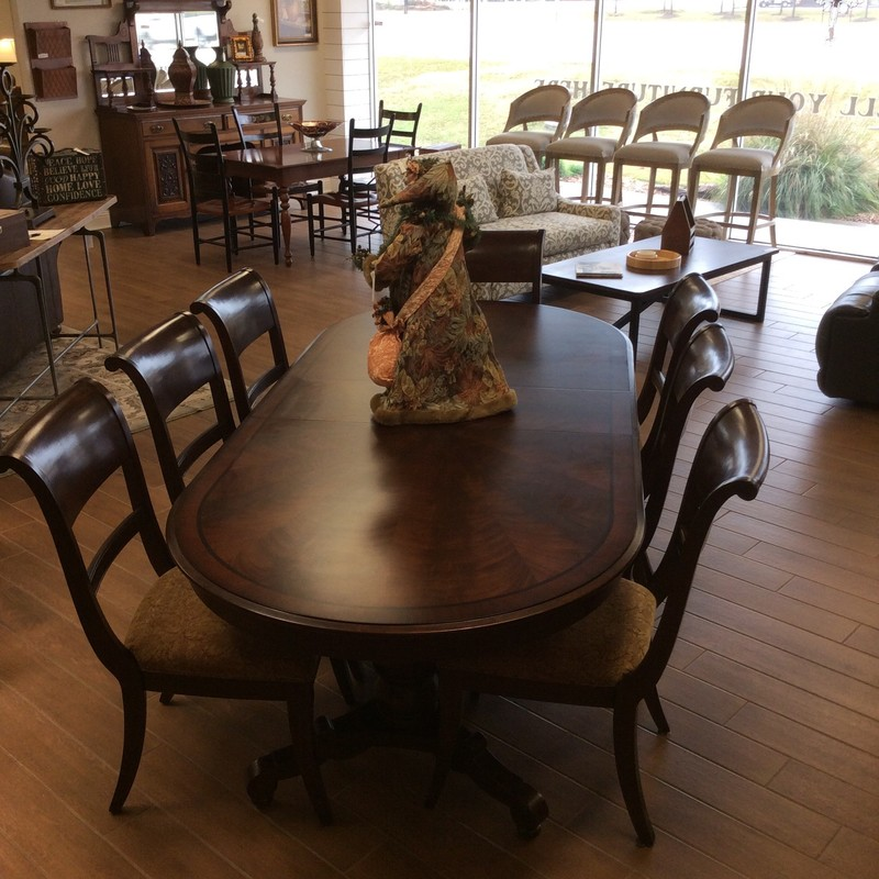 This dining room table by Lane features a mahogany wood finish, a double pedestal base, 2 leaves and 8 upholstered chairs.