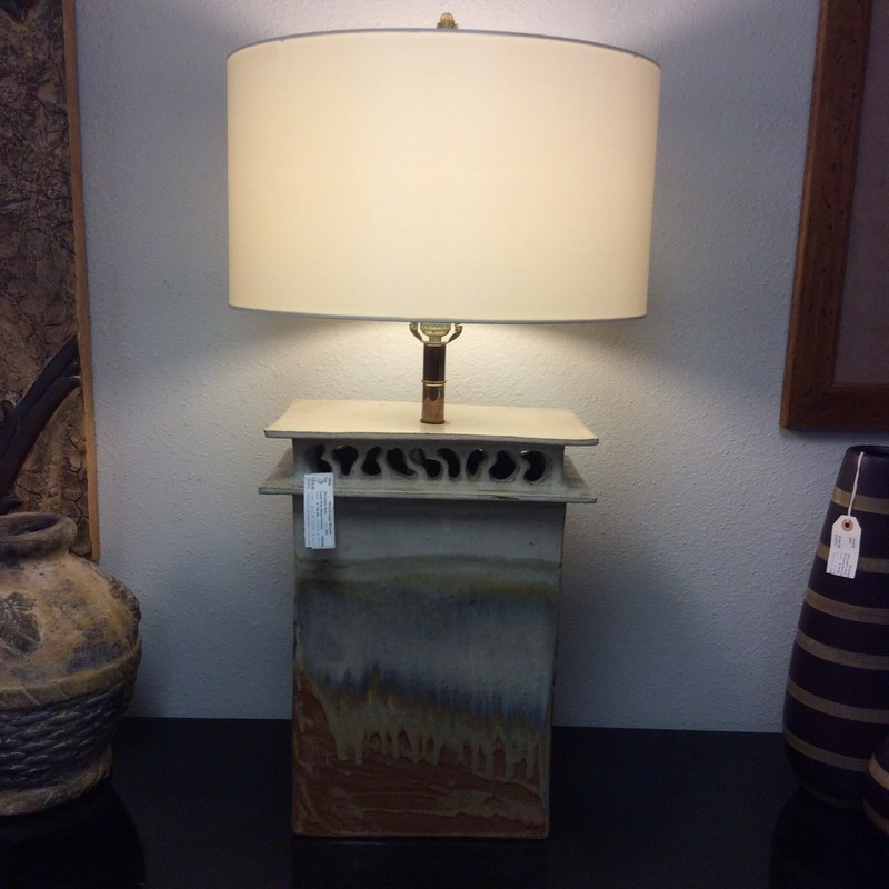 This is a really large, heavy lamp. The base is hand crafted, painted and glazed ceramic. It has an open design near the top, so the seperate light in the base shows through. Really unusual and only $125!!