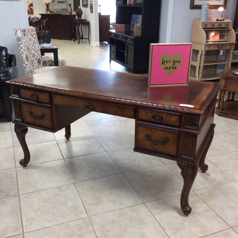 This is a really beautiful writing desk. It features a dark wood finish, is ornately and heavily carved. There are 2 side drawers that are actually file cabinets and the middle drawer will accomodate a keyboard. One leg has seen some damage which the price reflects.