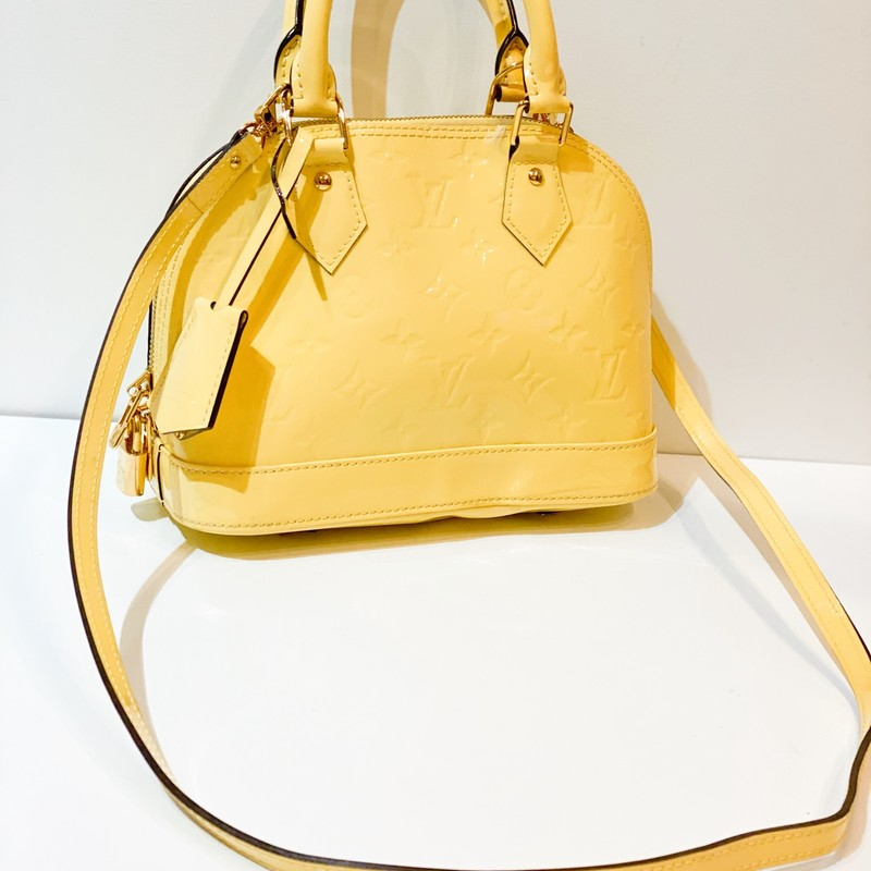 "Louis Vuitton Yellow Alma, Yellow, Size: Small<br /> Yellow monogram Vernis leather Louis Vuitton Alma BB satchel with brass hardware, dual rolled top handles, single flat detachable shoulder strap, tonal canvas lining, single slip pocket at interior wall and two-way zip closure at top. Includes clochette, lock and keys.<br /> Shoulder Strap Drop: 22.5""<br /> Handle Drop: 3.25""<br /> Height: 7""<br /> Width: 9""<br /> Depth: 4.5""<br /> Good condition.Bag is very clean inside and out. Indentation on bottom of bag, hard to see unless you look closely at bottom. This bag is a steal!"