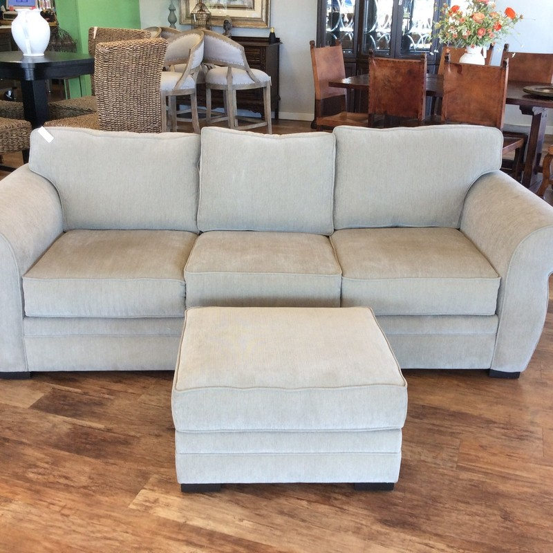 Originally from Macy's,this upholstered sofa with matching ottoman is very nice and in near-perfect condition. Contemporary in style but neutral enough to fit into just about any decotative style. It features a taupe colored upholstery with a matching ottoman.