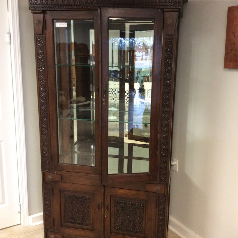 This is a really lovely curio cabinet from Indonesia. It was handmade of solid hardwood and features beautiful intricately carved accents. The lower cabinet has a single shelf. The upper curio has a mirrored back and bottom, as well as 2 adjustable glass shelves and internal lighting.