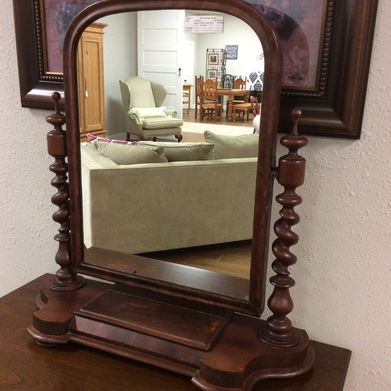 This vanity mirror has a vintagy, timeless, old world  look with a dark wood finish. The mirror pivots and is framed by a pair of barley twist columns. It also features a small felt-lined drawer. This would be a perfect piece atop a vanity as pictured here, a dresser or in a bathroom.