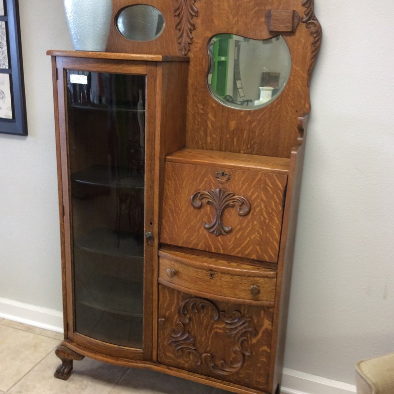 This is a darling antique secretary. It is made of solid golden oak, and has tiger oak veneers on the front. The left side is actually a curio cabinet, or could even be used for books. The right side has the drop-front desk, as well as a drawer and a lower cupboard. The 2 small mirrors and the carved details make this piece special!