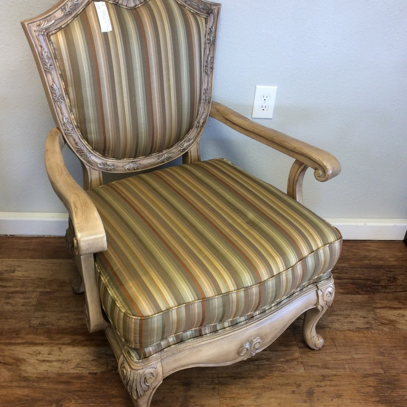 This upholstered arm chair is in fabulous condition. The style is Queen Anne-like. The upholstery is muted, earth toned stripes and the throw pillow is reversible floral-to-stipes.  The wood base and trim has an antiqued whited finish. There is also a matching floral sofa that is available for purchase seperately.