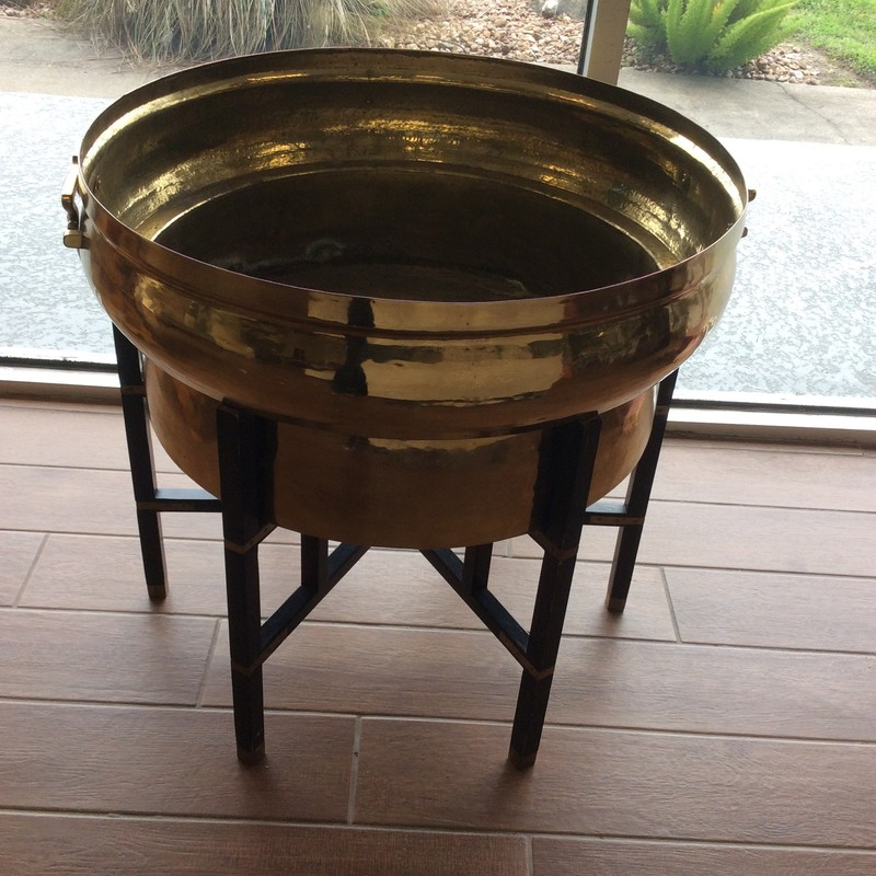 This is so cool! It is 2 pieces. The stand itself is 6 legged, and made of wood, with a black finish and brass details. The planter is solid hammered brass, and has handles on both sides. It looks alot heavier than it actually is, but boy oh boy, is it pretty!