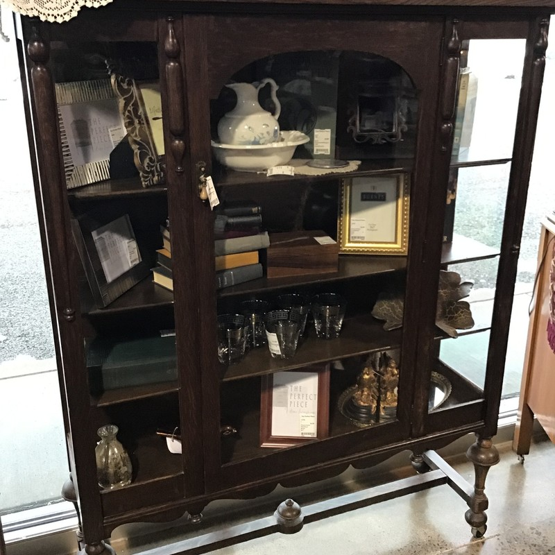 "This dark wood antique cabinet has a glass front to showcase your collectibles or books! It has a glass door and wooden shelves. The bottom has casters for easy moving!<br /> Dimensions are 62"" x 21"" x 34"""