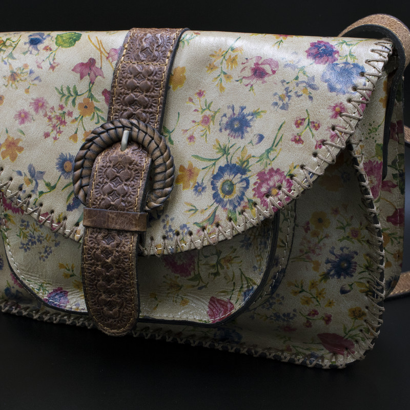 Patricia Nash Prairie Rose Collection NWT.  Scattered with flowers in pink, blue and gold set against a muted beige bacground.  Cognac distressed leather trim and brushed brass hardware.  $199 Retail<br /> Crossbody