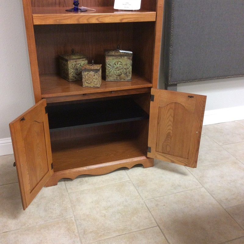 BARGAIN ALERT! This little bit older display cabinet is still in great shape and at $125. what's not to love? Constructed of golden oak and a veneer it features 3 display shelves, one is adjustable. The bottom has an additional adjustable shelf enclosed by handsomely carved cabinet doors with shiny brass hardware. Topped off with an interior light.  Won't last long!