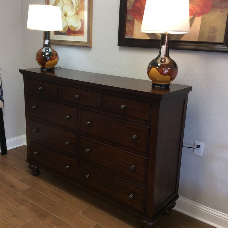This dresser features a dark wood finish and 9 spacious drawers. The hardware has a brushed, bronzed vintagy look. Very nice and classically designed.
