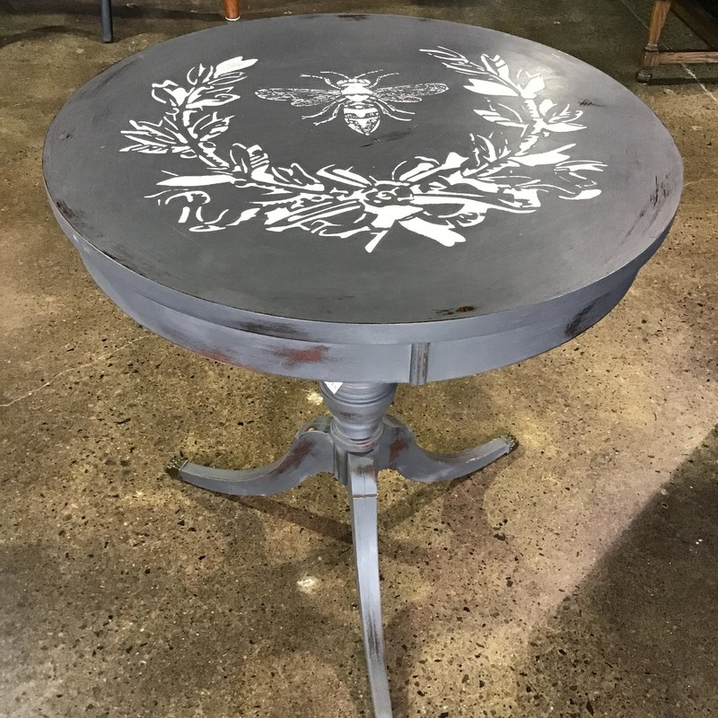 "This vintage drum table with 3 legs has been updated with a dark gray paint and the top has a bee and leaves stenciled on it in a cream paint. Pretty table for next to a bed, sofa or chair!<br /> Dimensions are 23-1/2"" x 26"""