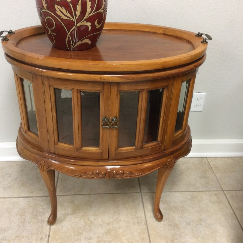 This adorable chocolate table is in excellent condition. It features solid wood construction and has a light cherry finish. The top has a removable tray that fits snuggly on the table top, itself. There are 16 beveled glass panels that, together with the wood, make up the outer perimeter of the cabinet. There are 2 small doors in the front, and the carved details are to die for!! This won't last long, so hurry in to see it for yourself.