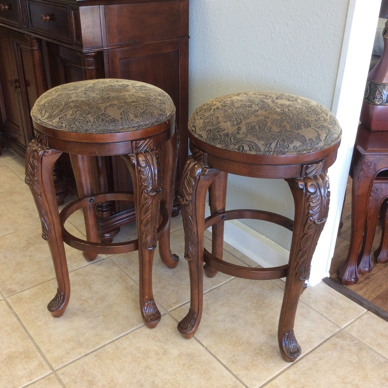 Great pair of barstools here! They are solid, substantial and sturdy. Ornately carved legs feature detailed woodwork. The seats are elegantly upholstered in a sage and goldy/ taupy floral pattern. Best of all, they swivel!