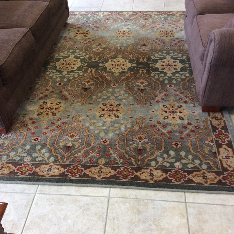 This pretty KARASTAN rug looks brand new! It is 6 feet by 9 feet, and has a medallion and floral pattern. While there are many colors represented here, it is primarily shades of gray, with brick, aqua, gold, brown and beige accents.