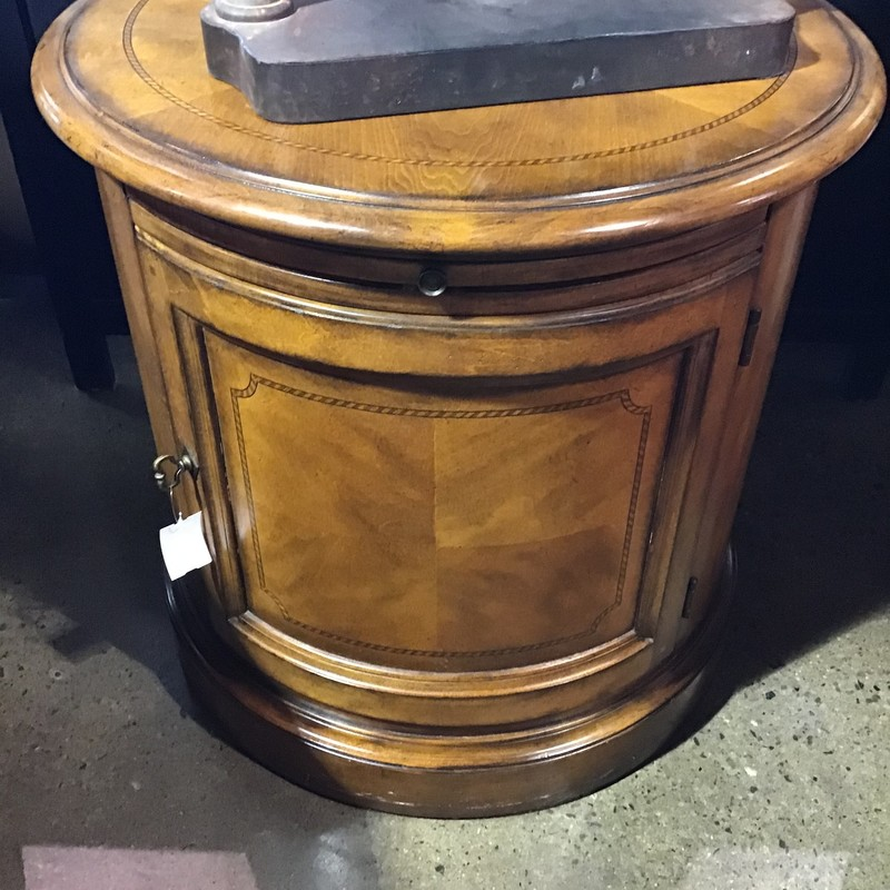 "Are you looking for that perfect storage piece that can serve as an end table but has storage? This round table might just be perfect! It has a cabinet below that offers tons of storage and a pull-out try when you need to extra space to set things on!<br /> Dimensions are 27"" x 27"" x 26"""