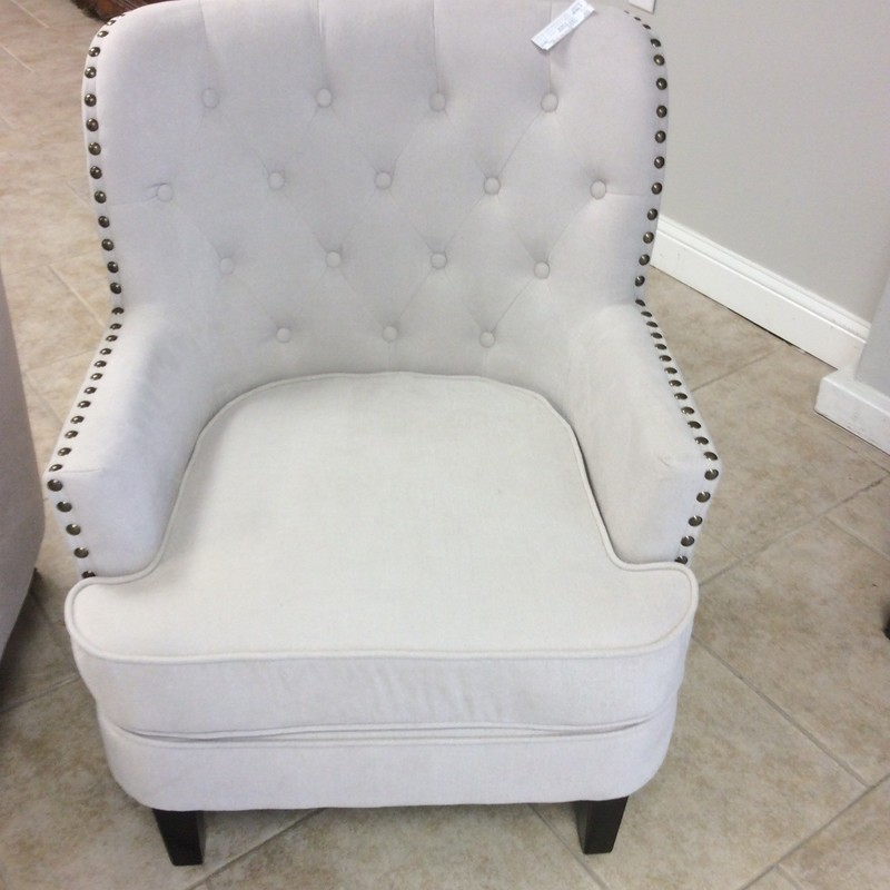 This pretty little arm chair is only about a year old. The oyster colored upholstery is in immaculate condition and the chair itself sits very comfortably. The back is tufted with 16 buttons, and there are large burnished brass nailhead accents on the arms, up the sides and across the back. Best of all, there is an identical twin that is available for purchase separately!