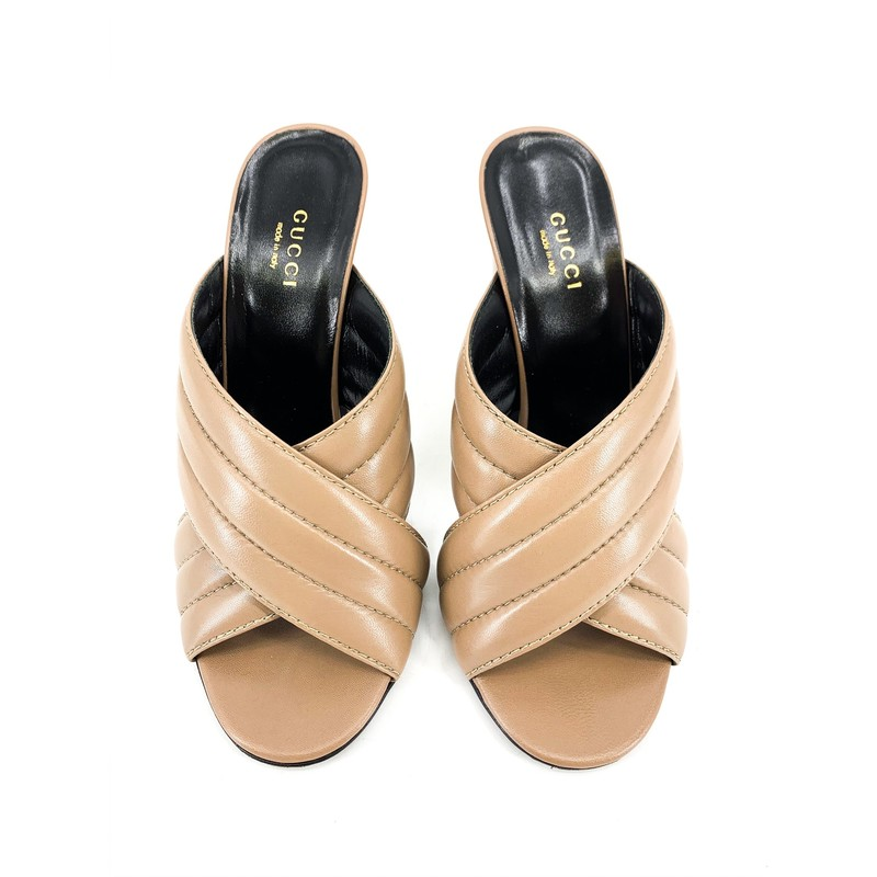 Gucci Taupe Criss-Cross Mule Heels<br /> <br /> DETAILS<br /> - Taupe quited leather, stitched bands<br /> - Black interior and soles<br /> - Peep toe<br /> - Condition: Excellent! Some wear on soles<br /> - Marked as 38 1/2, US size 8<br /> <br /> MEASUREMENTS<br /> - Heel: 4 1/2 in.