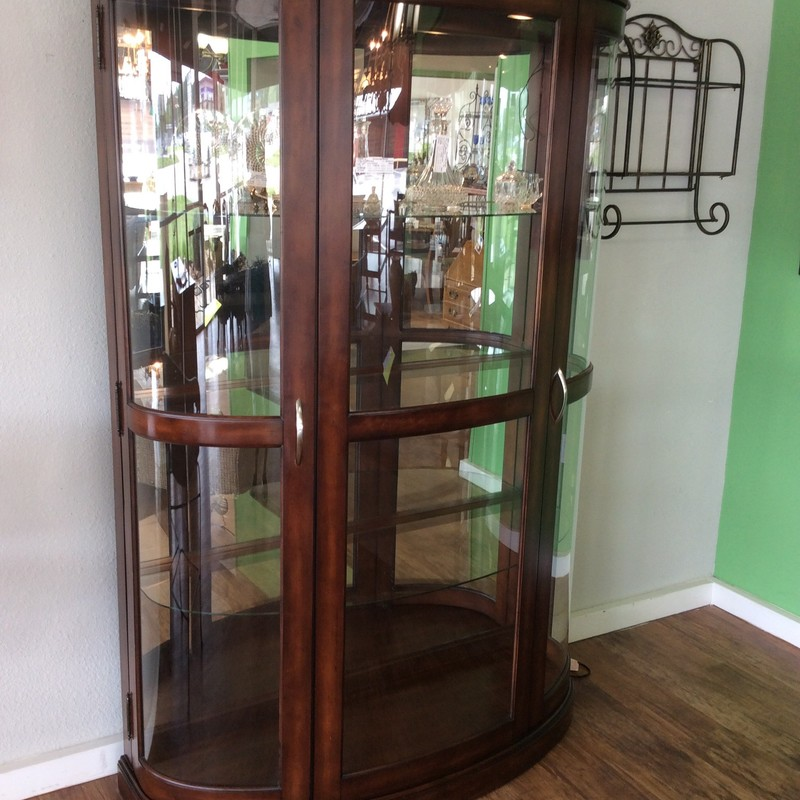 "This elegant looking curio cabinet is quite large. There are 3 panes of curved glass and they are surrounded by what appears to be wood that has a pretty cherry finish. There are 3 roomy shelves and it is lighted inside with ""touch"" technology. There is some minor damage around the bottom of this piece, so it is priced at only $595!"