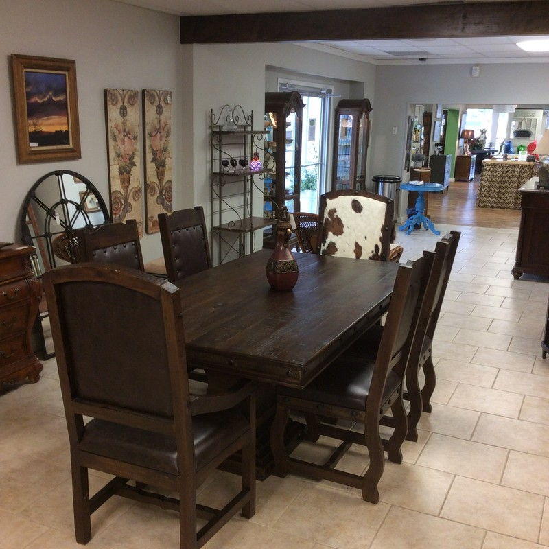 This dining room set is gorgeous! From Rustico Sierra it re-defines rustic! The table top is dark pine and plank style with a double pedestal  base. Six large, hefty chairs come with the set in the same dark pine. Four of them are upholstered in leather and the two Captain's chairs feature a cowhide seatback. It's a stunning set for lovers of the rustic style.