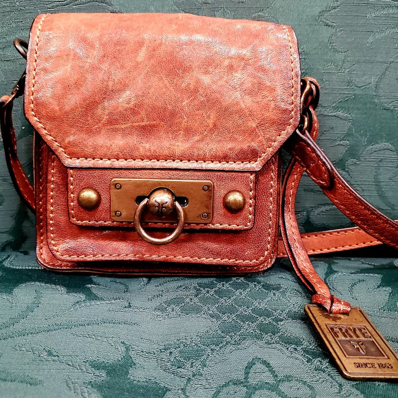 "Frye AdjustableCrossbody bag<br /> Approx. 6"" X 6""<br /> Strap at longest Approx. 26""<br /> Whiskey in color<br /> One zipper inside pocket<br /> One compact compartment under flap<br /> Dust Bag<br /> New Scuffed variegated leather<br /> Sturdy front flap<br /> Brass hardware"