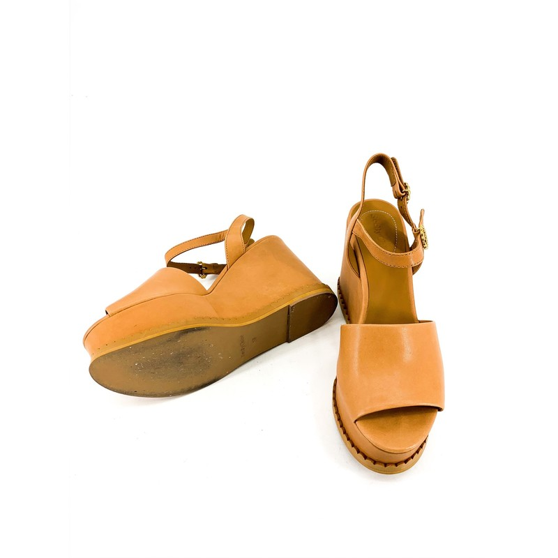 See By Chloe Tan Chunk Platform Wedge Sandals<br /> <br /> DETAILS<br /> - Tan platform peep toe wedge<br /> - Gold flower shaped hardware<br /> - Double adjustable strap, on ankle and back<br /> - Scalloped edging<br /> - Lightweight!<br /> - Condition: Good! Wear on sole and some interior marks<br /> <br /> MEASUREMENTS<br /> - 4 in. platform wedge