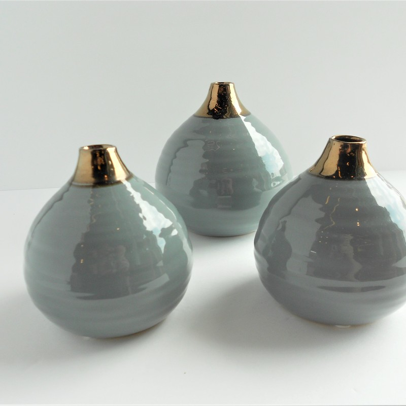 Sleek and modern, these ceramic vases boast a luxurios sheen and gold detailing.