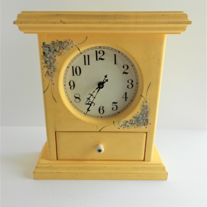 cheerful and fun this hand painted wooden clock features a pull out drawer and delicate floral detailing