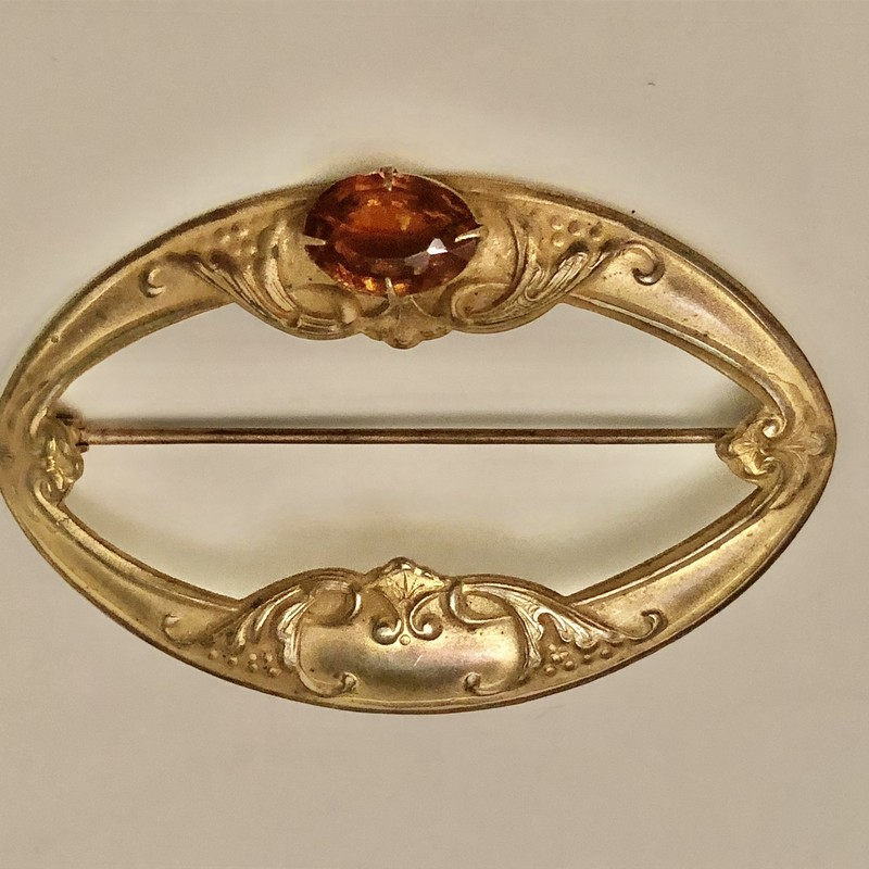 "Victorian Brass on copper Sash Pin with amber glass bezel set cabochon.  Original c-clasp. Size: 3"" X  2\"""