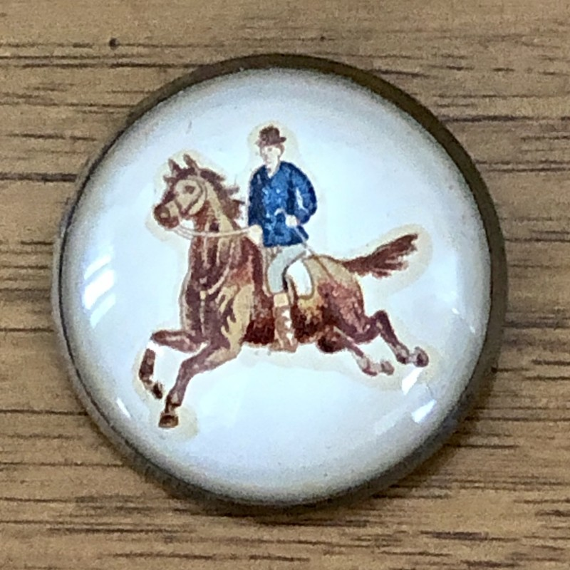 Victorian c.1980-1910 Domed convex glass horse Bridle Rosette Brooch.<br /> Galloping out of a creamy off-white background, this spirited galloping horse and rider are a Victorian die-cut made as a bridle rosette brooch style pin. At 1-5/8 inches across, the clear artwork is an eyecatcher. The back of the rosette was designed to slide a horse bridle strap through.