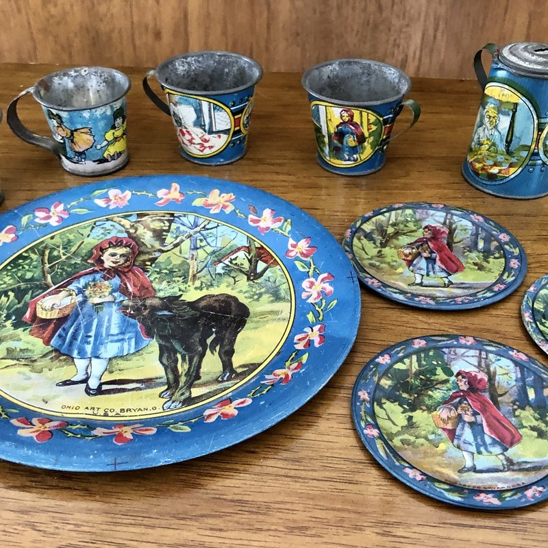 "Ohio Art Tin Litho ""Little Red Riding Hood\"" Tea Set c.1930s.<br /> - 1 Large plate 6 1/8\"" in diameter<br /> -3  Small plates 2 3/4\"" in diameter<br /> - 4  2\"" inch cup with handles<br /> - 1 2 1/4\"" teaot with lid<br /> This set has been used and has paint loss consistent with a 1930s set."