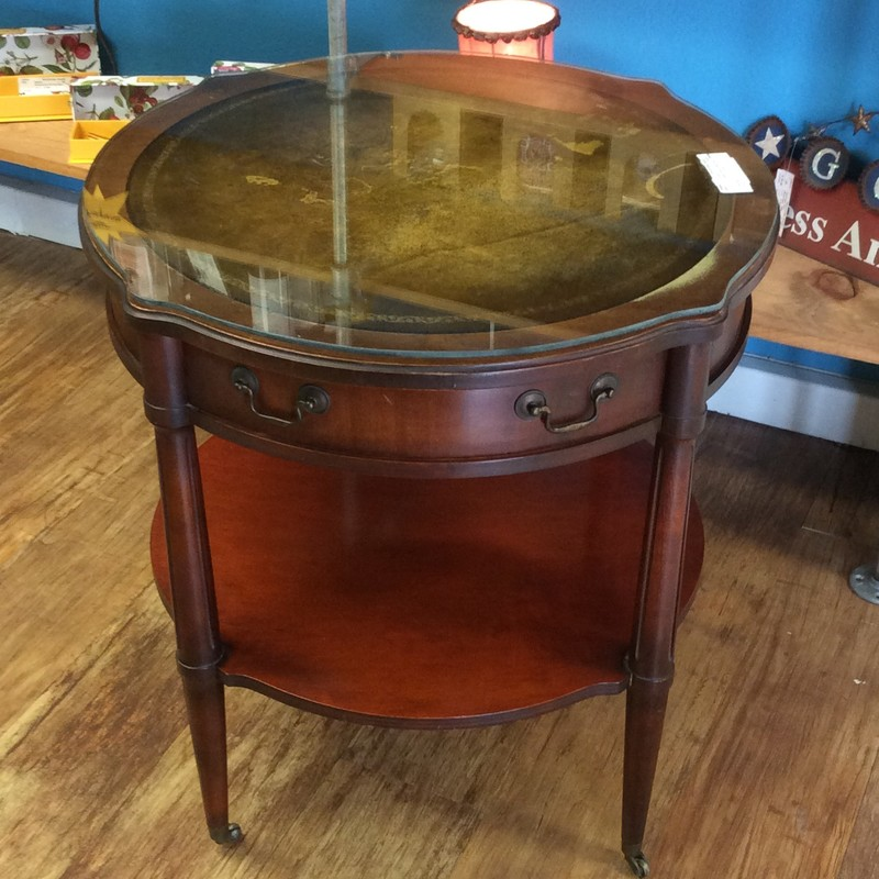 This darling little ANTIQUE table features solid wood construction with an inlaid leather top. There is also a glass topper. It also has a single drawer, as well as a lower display/storage shelf. Best of all, it has tiny little casers on each leg, so that you can move it around easily.