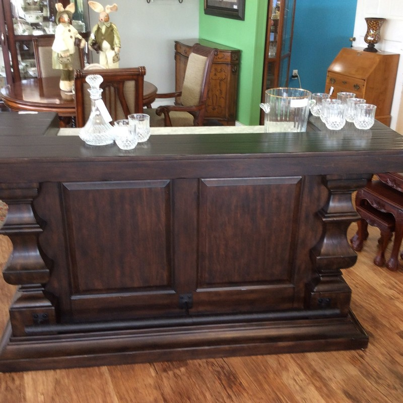 This is a really nice looking POTTERY BARN, stand-alone bar. It features solid wood construction with an espresso finish. There is an open area with a single shelf, as well as a cupboard (disguised as 3 drawers!) with an adjustable shelf. There is a drawer and a pull out tray up top, as well. The top surface is a lovely piece of white and gray marble. There is also a foot bar on the other side, for your seated guests.