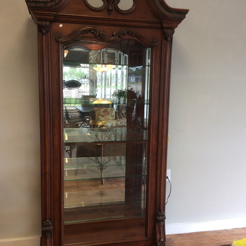 This pretty curio cabinet features solid wood construction with a cherry finish. Inside, it has a mirrored back, lighting, and 5 adjustable glass shelves, each with plate grooves. The front is a sliding door that will open in either direction. The carved wood details put this cabinet over the top. They is a key, too!